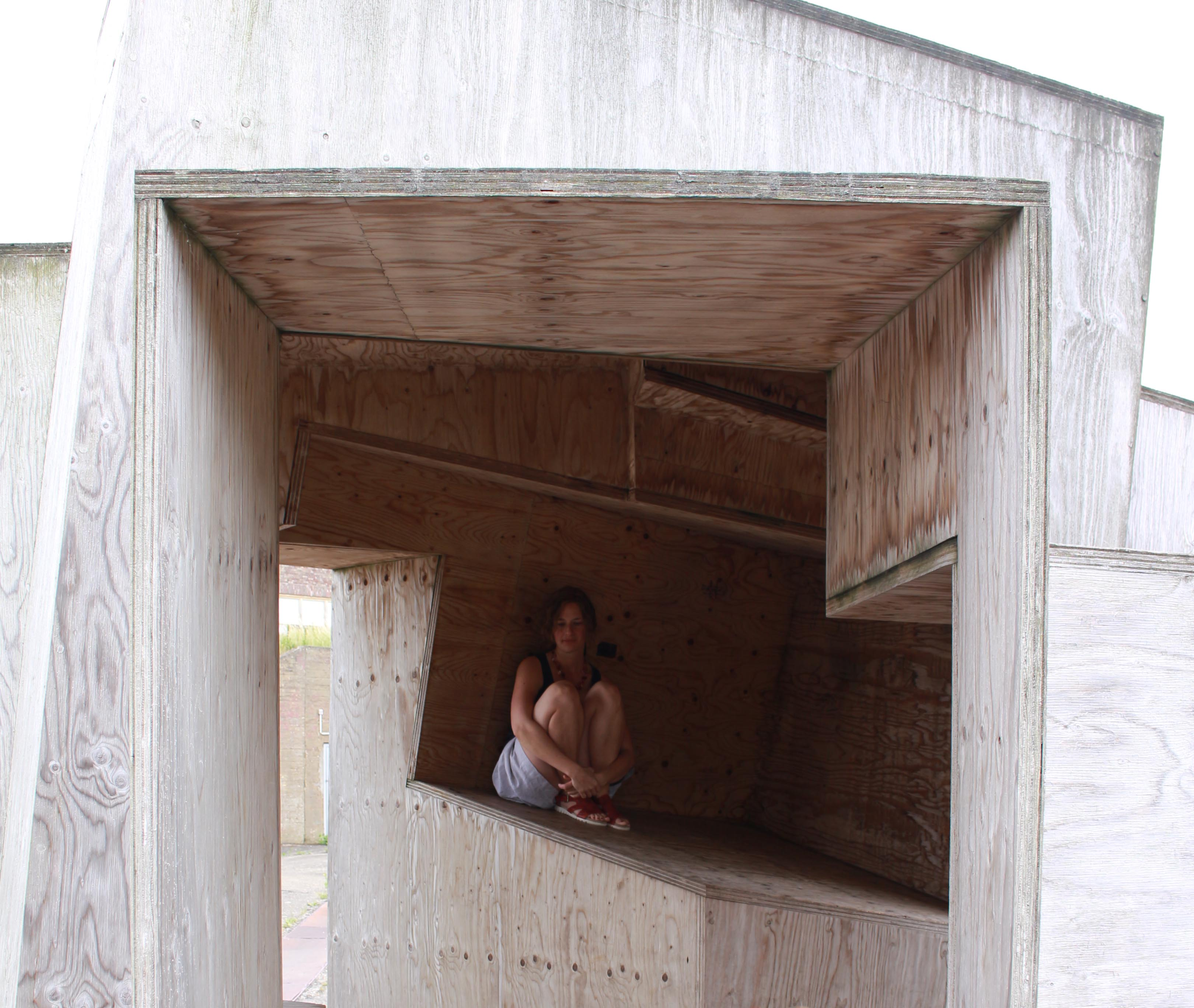 Zusammengekauerte Frau in kompliziert geformter Holzkiste