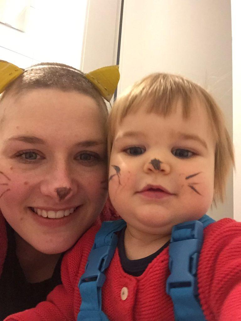 Frau mit kurz rasierten Haaren in Katzenkostüm mit Baby