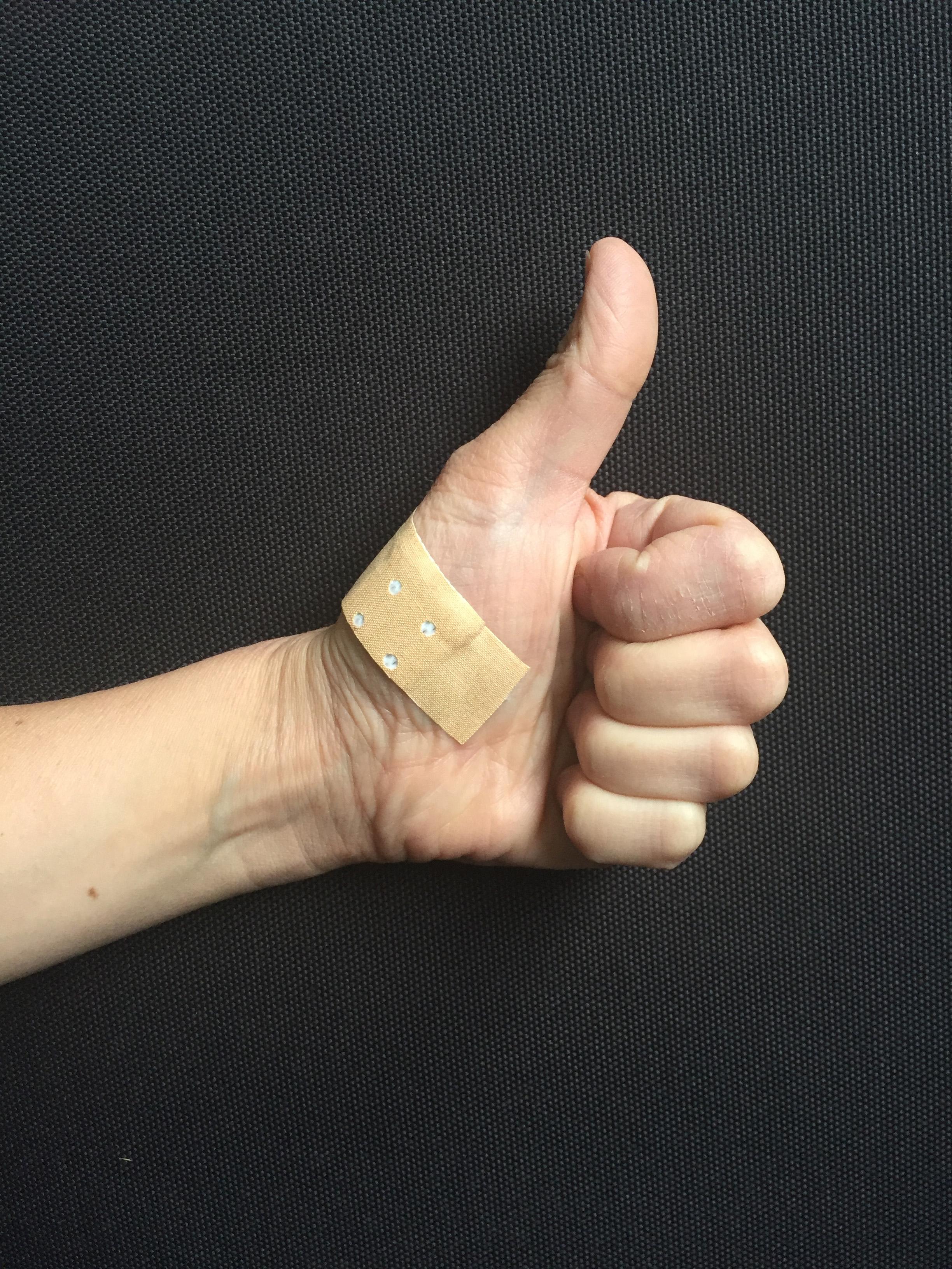 Hand mit hochgestrecktem Daumen mit Pflaster
